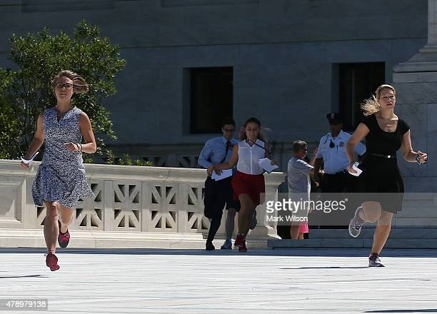 Interns run with a court decision to reporters stationed outside of the US Supreme Court June 29 2015 in Washington DC Today the high court ruled on...