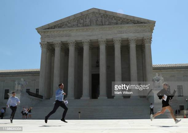 Interns run with decisions released by theU.S. Supreme Court, on June 27, 2019 in Washington, DC. The high court blocked a citizenship question from...