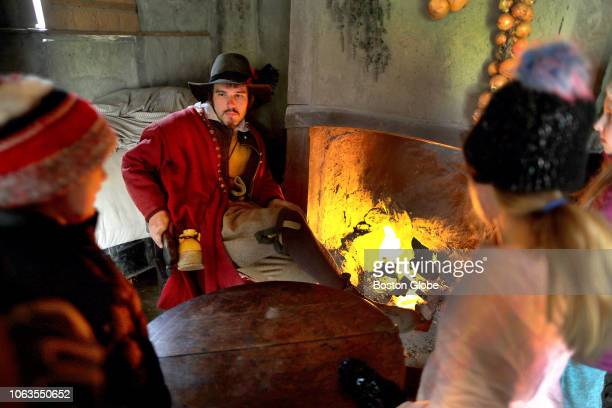 Interpreter Phillip Messier sits by a fire in one of the homes as children observe at Plimoth Plantation in Plymouth MA on Nov 15 2018 On a recent...