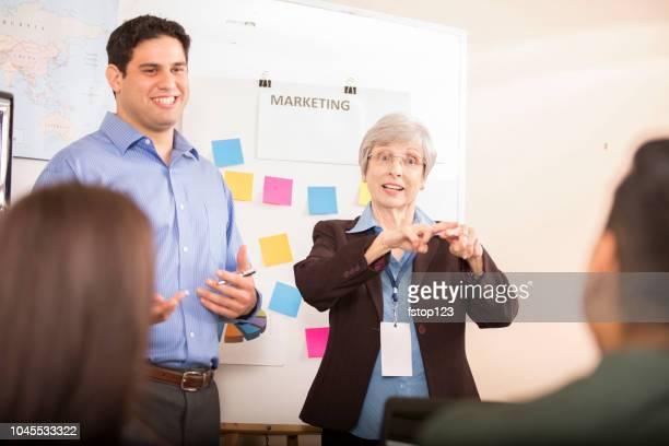interpreter ondertekening tijdens zakelijke bijeenkomst. - gebaren stockfoto's en -beelden
