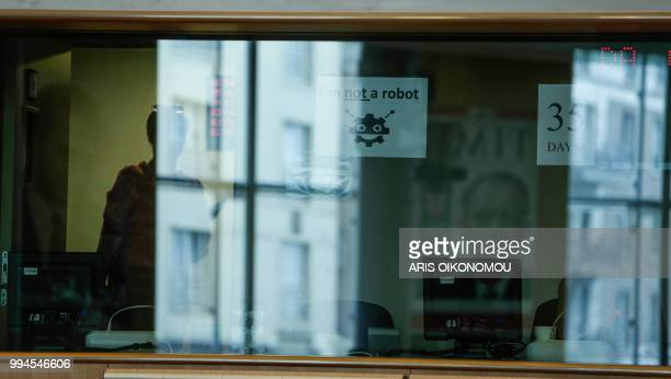 Interpreters at the European Parliament stick 'I am not a robot' and '95 days' banners on the windows of the their booths after 35 days of strike...