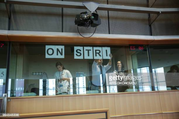 Interpreters at the European Parliament stick 'On strike' banners on the windows of the their booths after 35 days of strike before the arrival of...