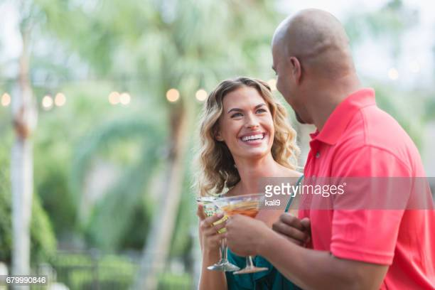 interracial couple drinking cocktails outdoors - margarita drink stock photos and pictures