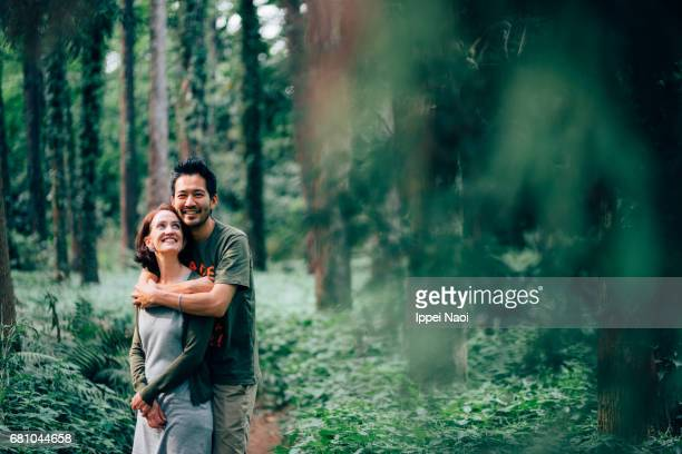 Interracial couple embracing in forest