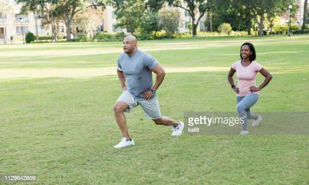 interracial couple exercising together in the park - hand on hip stock pictures, royalty-free photos & images