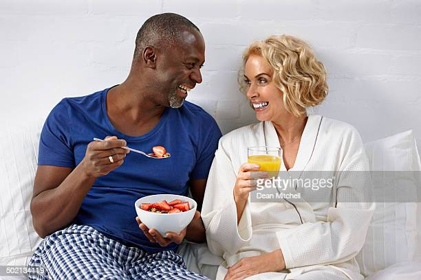 Interracial couple having healthy breakfast on bed