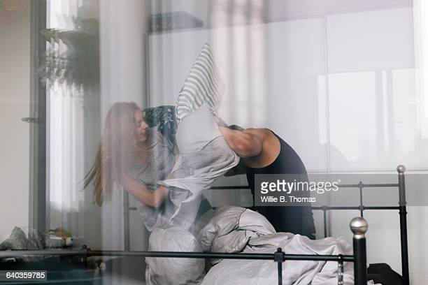 interracial couple having pillow fight on bed - naughty wife stock photos and pictures