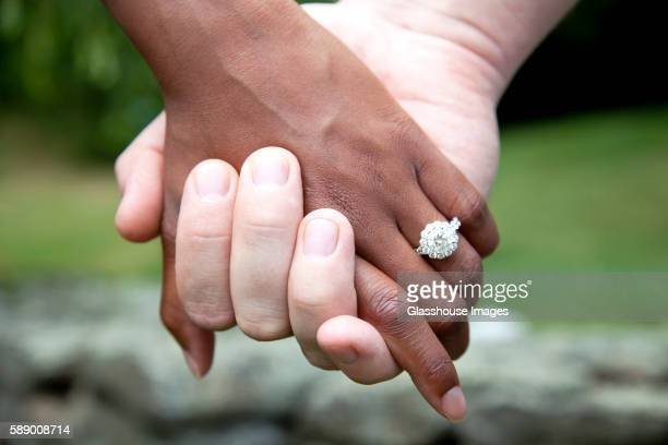 interracial couple holding hands and diamond engagement ring, close-up - engagement stock pictures, royalty-free photos & images