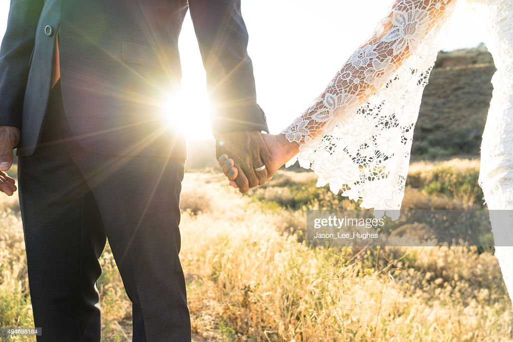 Interracial couple holding hands at wedding : Stock Photo