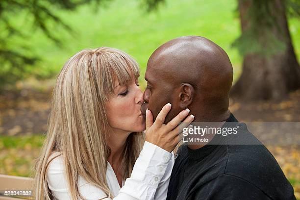 interracial couple kissing in a park; edmonton alberta canada - black women kissing white men stock pictures, royalty-free photos & images