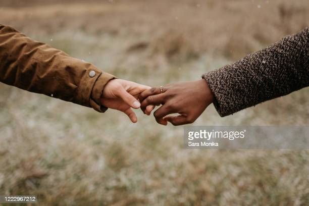interracial couple, man and woman holding hands, one wearing a gold wedding ring. - holding hands stock pictures, royalty-free photos & images