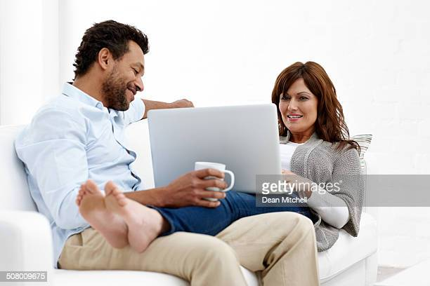 Interracial couple relaxing on a sofa with coffee and laptop