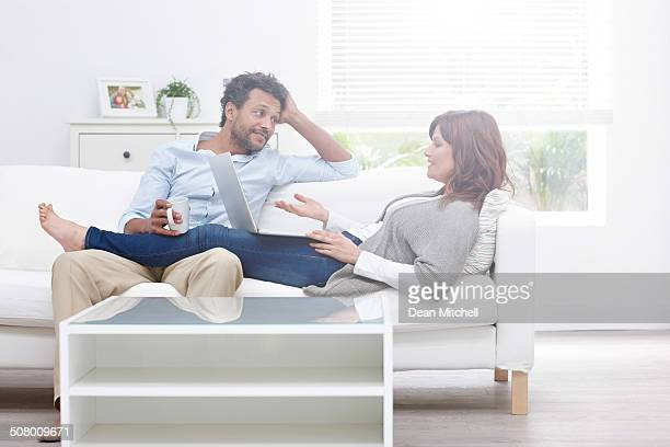 Interracial couple relaxing on sofa in free time