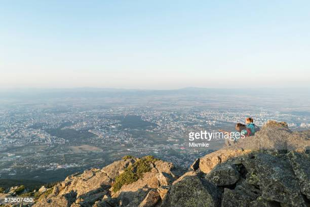interracial couple resting on the mountain peak and talking. - foothills stock pictures, royalty-free photos & images