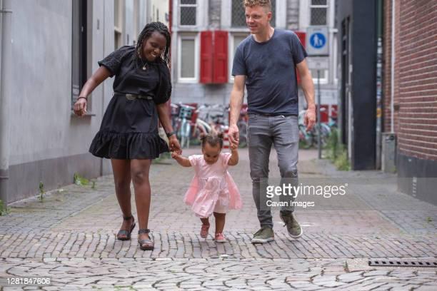 interracial couple teaching their toddler to walk - color blindness - fotografias e filmes do acervo