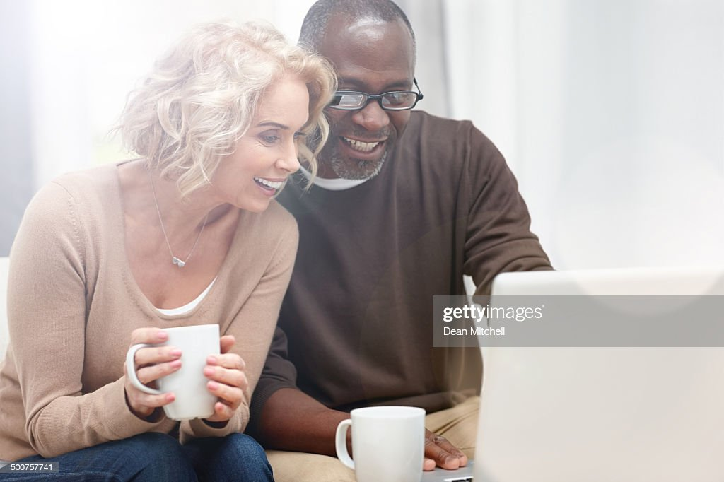 Interracial couple using laptop at home : Stock Photo