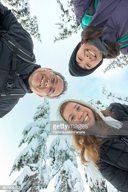 Interracial Family and Friends Looking Down, Snow Covered Tree Background