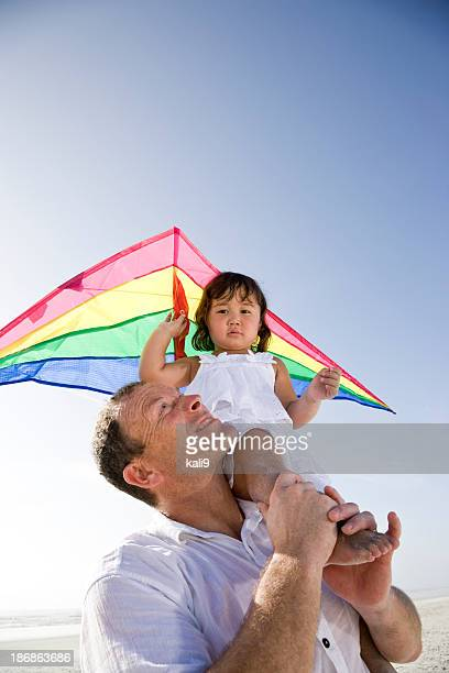 Interracial family, father and little girl having fun flying kit