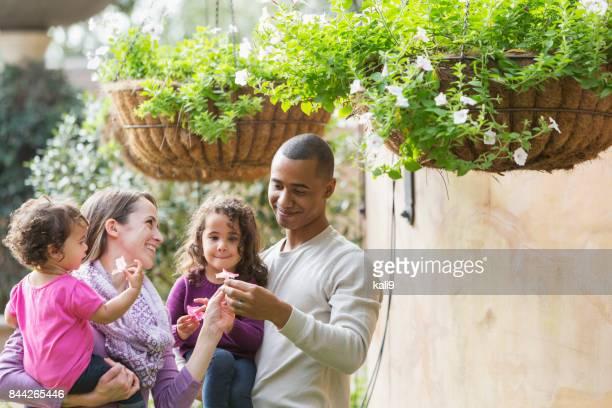 Familia interracial, dos chicas jóvenes, recogiendo flores
