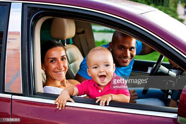 Interracial family with One year old child in a car