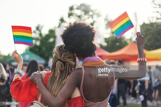 プライドパレードで虹の旗を振る異人種間の女性カップル - ゲイプライドのシンボル ストックフォトと画像