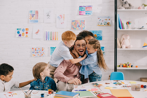 interracial kids hugging happy teacher at table in classroom 1016014374