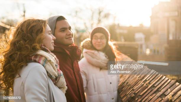 Interracial loving couple, teenagers, the beautiful Caucasian white 17-years-old long haired girl and handsome Latino Hispanic 18-years-old boy, and their friend, 15-years-old teenager girl, walking on the street, talking and having fun in the cold winter