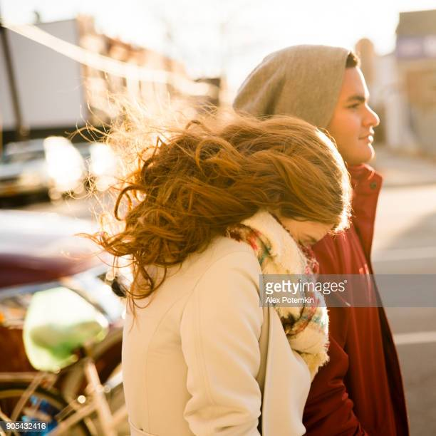 interracial loving couple, teenagers, the beautiful caucasian white 17-years-old long haired girl and handsome latino hispanic 18-years-old boy, walking on the street and having fun in the cold winter day - 14 15 years stock pictures, royalty-free photos & images