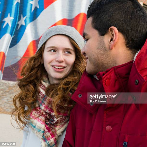 interracial loving couple, teenagers, the beautiful caucasian white 17-years-old long haired girl and handsome latino hispanic 18-years-old boy, walking on the street and having fun in the cold winter day - alex potemkin or krakozawr stock pictures, royalty-free photos & images
