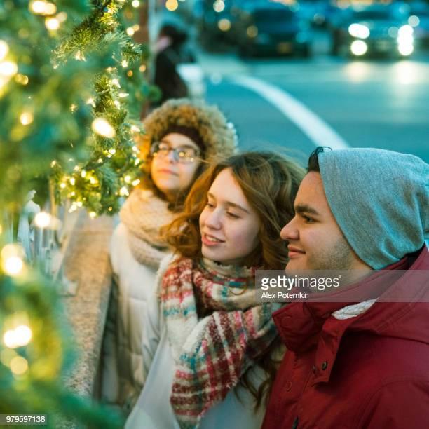Interracial Liebespaar, Teenager, der schönen kaukasische Weiße langhaarige Mädchen 17 Jahre alt und gut aussehend Latino Hispanic 18 Jahre alten Jungen und ihr Freund, 15 jährige Teenager Mädchen, Weihnachtsbeleuchtung und Spaß in der Kälte alle