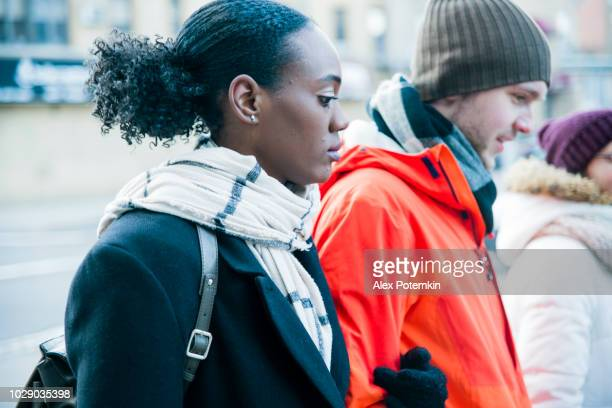 Interracial loving couple, the beautiful Black young woman and handsome young man, walking on the street and having fun in the cold winter day