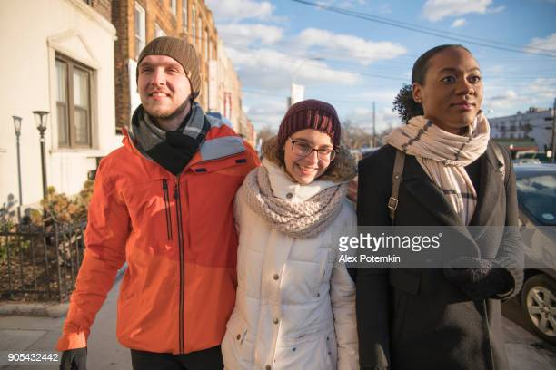 Interracial loving couple, the beautiful Black young woman and handsome young man, with their friend, 15-years-old teenager girl, crossing the street in the cold winter day