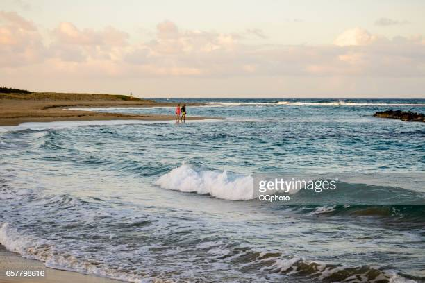 interratial couple walking on a beautiful beach - ogphoto stock photos and pictures