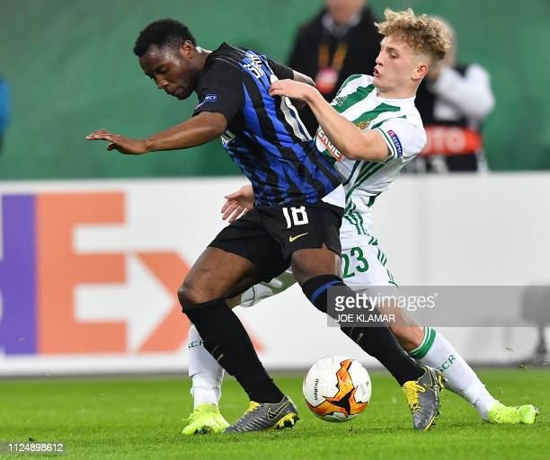 Inter's Kwadwo Asamoah and Rapid's Manuel Thurnwald vie for the ball during the UEFA Europa League round of 32 firstleg football match between Rapid...