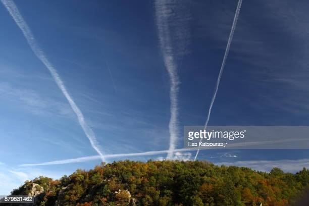 Intersecting contrails in clear sky over tree-covered mountain in Zagori, Greece