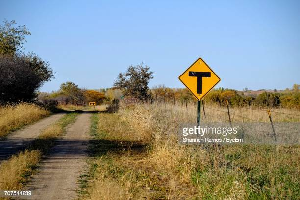 T Intersection Sign On Grassy Field By Dirt Road Against Blue Sky