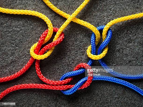 intertwined multicolored ropes - tied knot stock photos and pictures