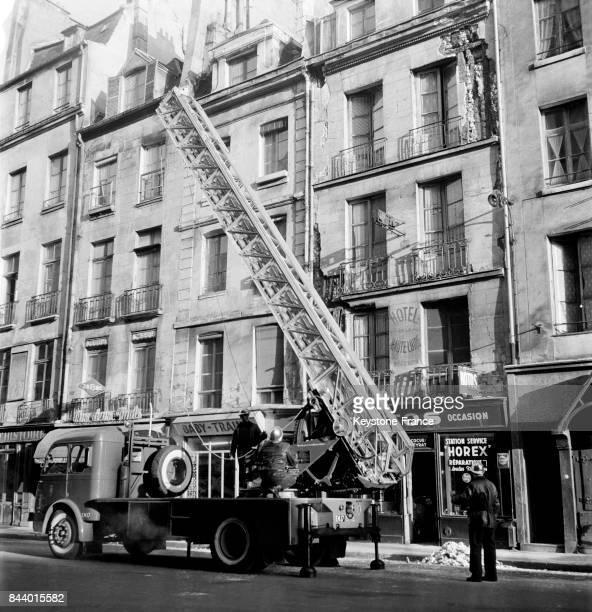 Intervention des pompiers qui viennent de détacher les morceaux de façade sur le point de tomber rue du PetitPont dans le Ve arrondissement à Paris...