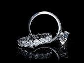 Interwoven diamond engagement ring, wedding ring on black background