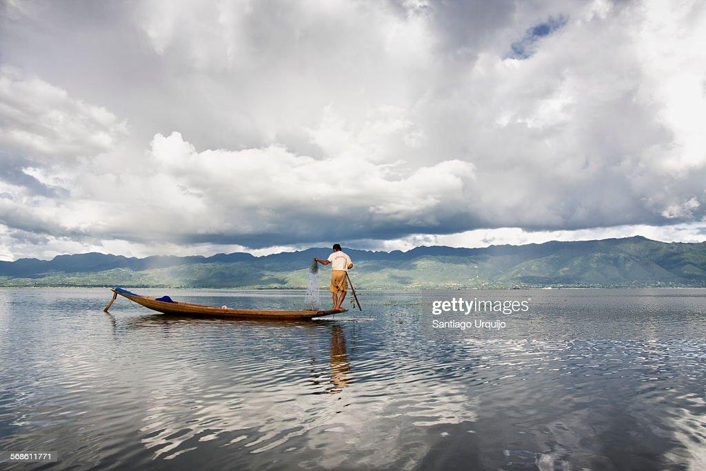 Intha fisherman casting a fishing net in Inle Lake : Stock Photo
