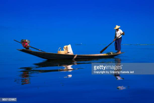 intha fisherman is rowing his both in inle lake, myanmar. - myanmar culture stock pictures, royalty-free photos & images