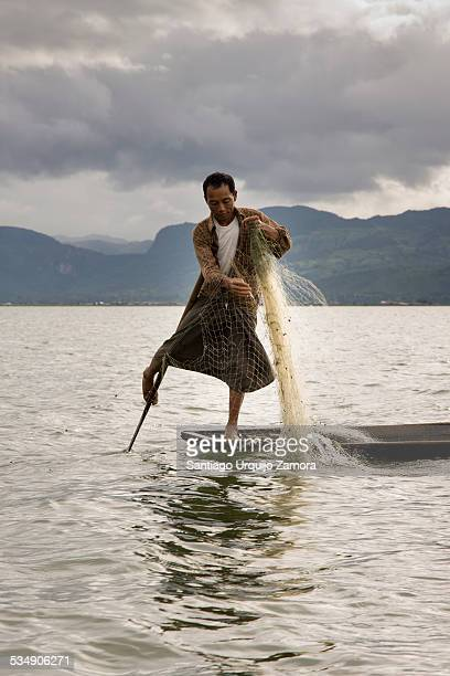 Intha leg rowing fisherman casting his fishing net from his wooden pirogue Inle Lake Shan State Myanmar Standing on the stern on one leg and wrapping...