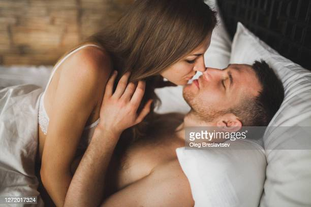 intimate couple in bed. kissing with passion and desire. young lovers on honeymoon. - privacy stock pictures, royalty-free photos & images