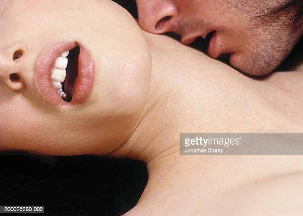 intimate couple, man kissing woman's neck, close-up - erotische stockfoto's en -beelden