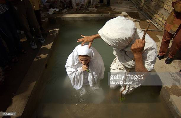 Intithar Manssur 26yearsold stands in water as she is baptized by Sheik Muthana Majid a Mandaean Sabian cleric at a postnuptial baptism ceremony May...