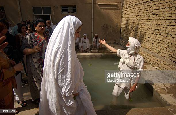Intithar Manssur 26yearsold walks towards the baptism pool to meet Sheik Muthana Majid a Mandaean Sabian cleric for a postnuptial baptism ceremony...