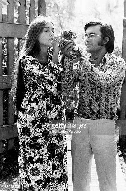 Into a garden the Italian singer Al Bano born Albano Carrisi and his young wife Romina Power are tenderly playing with a tabby kitten Romina's...