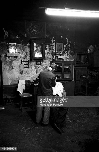 Into a shabby barber shop illuminated by a neon a barber seen from behind is working on a client the shop is housed in the bare room of a private...