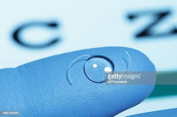 intraocular lens on gloved finger. intraocular lens is an artificial lens surgically implanted in the human eye following extraction of the natural crystalline lens clouded by cataract. - implant stock photos and pictures