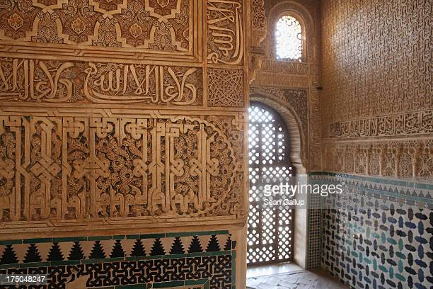 Intricate plaster work with writing in Arabic and tiles decorate a room in the Nasrid Palaces at the Alhambra on July 23 2013 in Granada Spain...